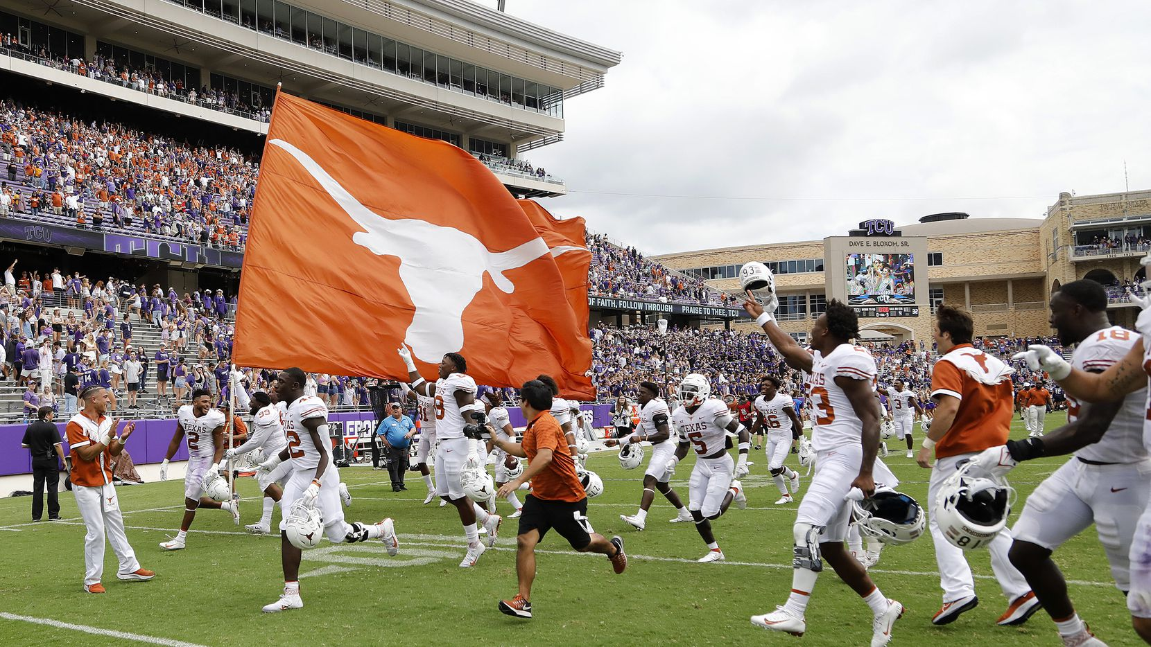 The Texas Longhorns take the field with a spirit flag after their victory as the TCU Horned Frogs hosted the Texas Longhorns on Saturday, October 2, 2021, at Amon G Carter Stadium in Fort Worth. (Stewart F. House/Special Contributor)