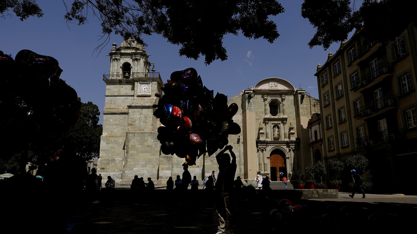 A balloon vendor is silhouetted against the Cathedral of Our Lady of the Assumption in Oaxaca.