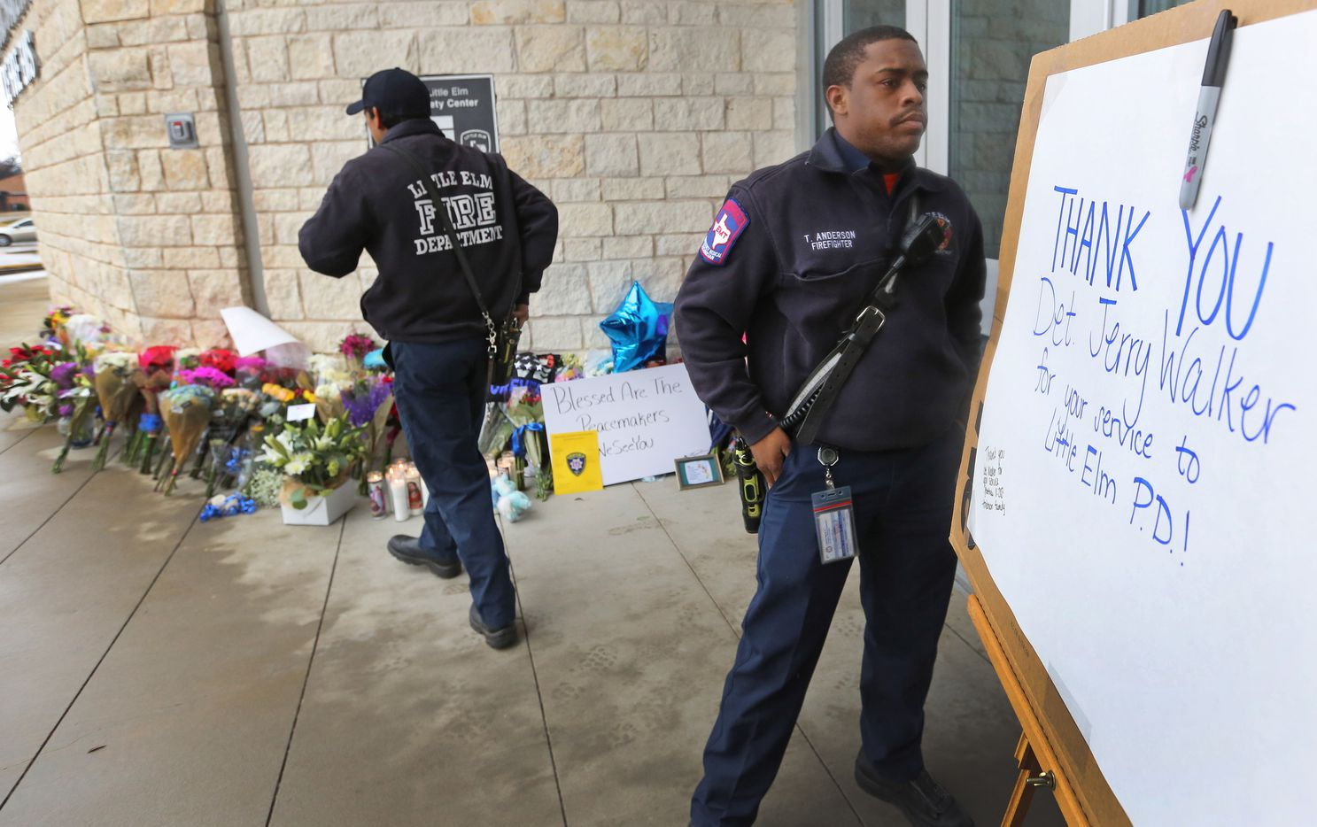 Little Elm firefighters Xavier Alonzo (left) and Terry Anderson help put up a placard to be signed by those visiting the makeshift memorial outside the Little Elm Police Department for Detective Jerry Walker. (Louis DeLuca/Staff Photographer)