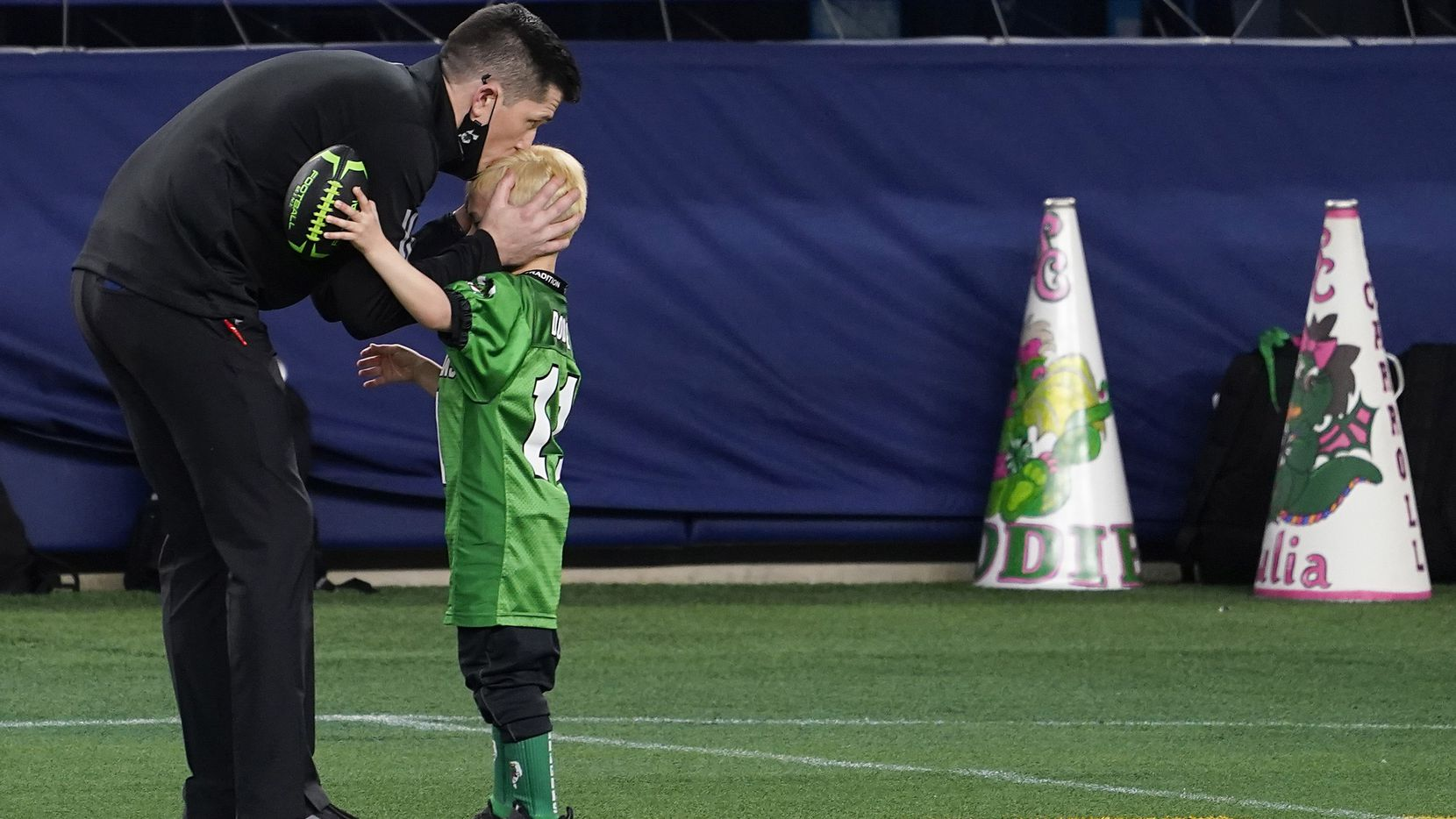 Southlake Carroll head coach Riley Dodge kisses his son Tate, 5, on the sidelines before the Class 6A Division I state football championship game against Austin Westlake, coached by his father Todd Dodge, at AT&T Stadium on Saturday, Jan. 16, 2021, in Arlington, Texas.