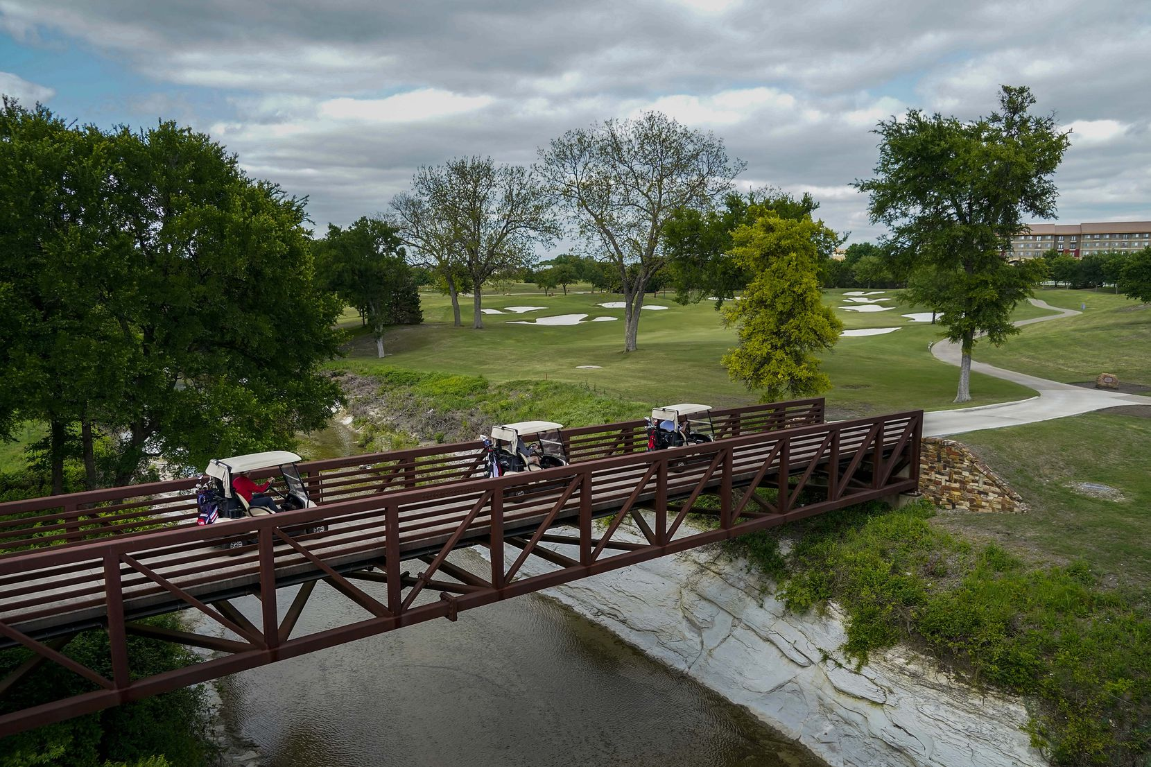 FILE - Players drive their carts across a bridge on the sixth hole at TPC Craig Ranch on Tuesday, April 14, 2020, in McKinney.