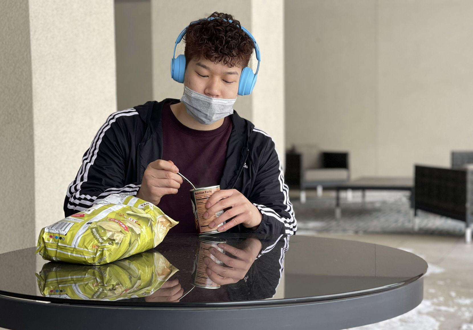 Jacky Chan eats a can of beans he warmed up on his apartment complex's gas grill in an outside courtyard on Tuesday, February 16, 2021 in Dallas. Chan said he didn't think the historic snowstorm that left millions without power would be this bad.