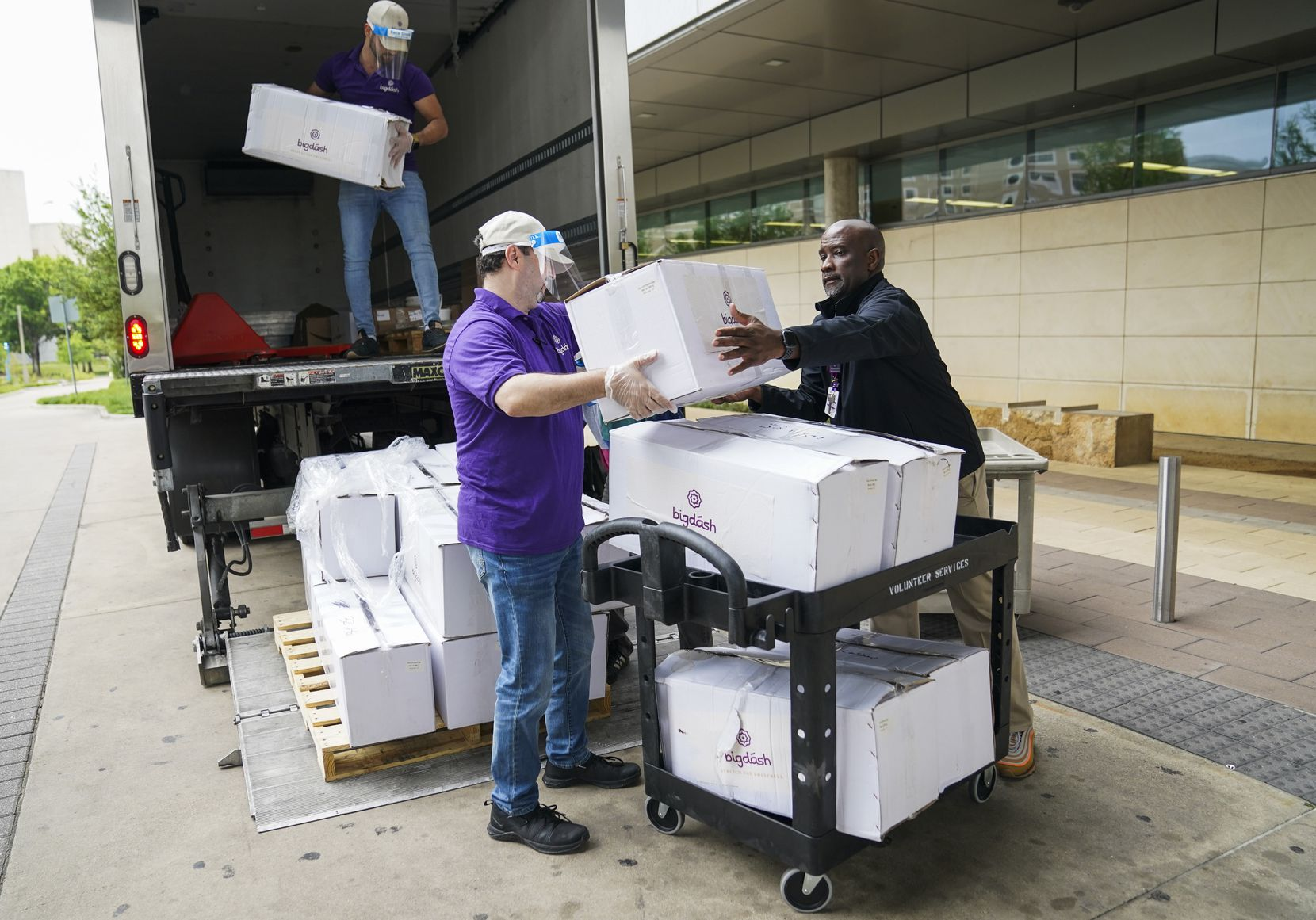Abdullah Mahdi (left) and Kareem Alrefaai (center) of  Bigdash Ice Cream & Pastries drop off desserts with guest services manager Delra Lacy at Parkland Hospital on Friday, April 17, 2020 in Dallas. Restaurants dropped off over 1,000 meals and 1,500 desserts for doctors, nurses and staff  The effort was organized by local Muslim business leaders. (Ashley Landis/The Dallas Morning News)