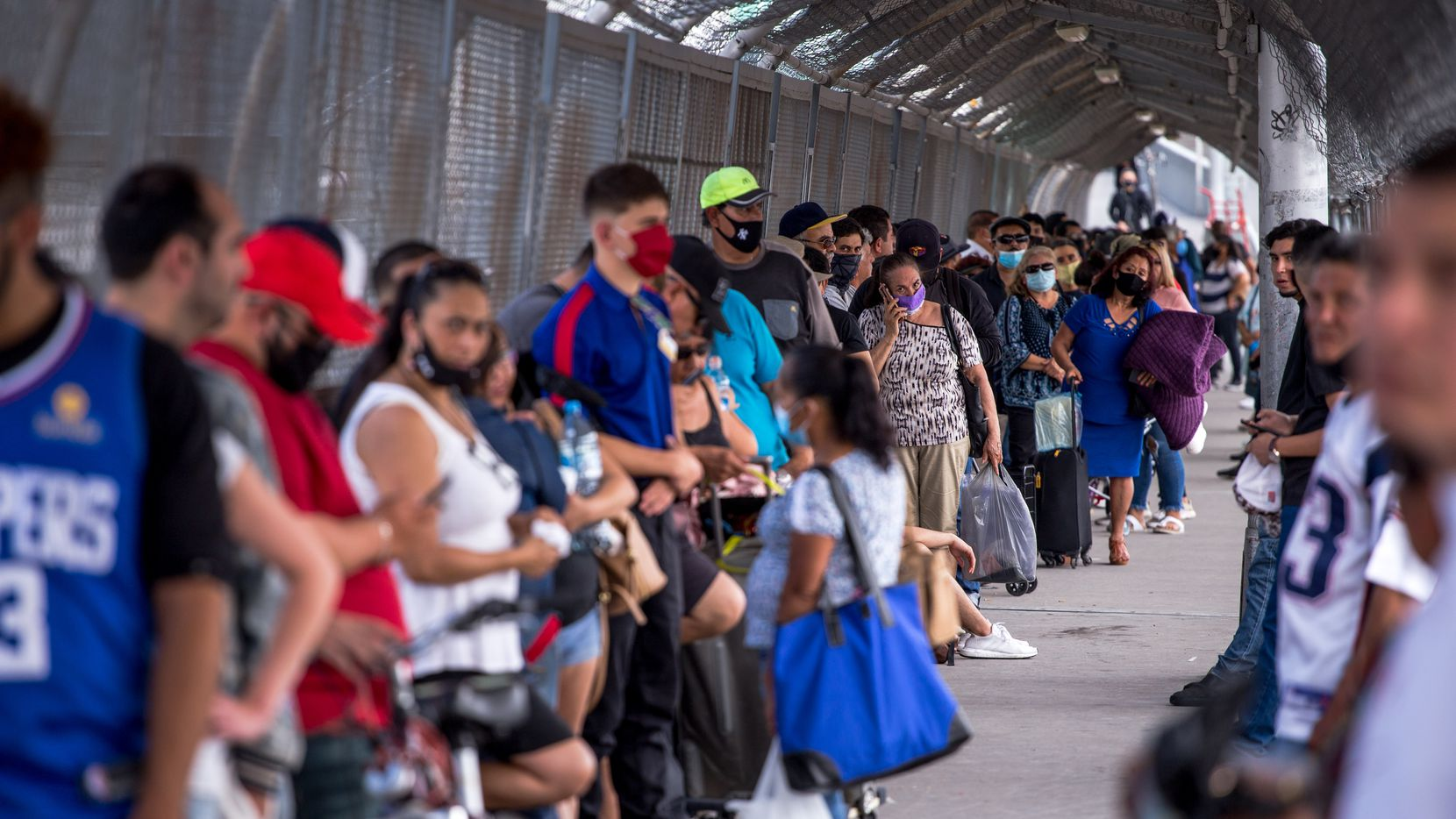 People wait in line to cross the border to El Paso, Texas through the Paso Del Norte Port of Entry in Ciudad Juarez, Chihuahua, Mexico, on Friday, June, 26, 2020.