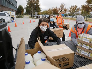 North Texas Food Bank's Ashlyn Stevens (left) of Dallas and volunteer Sean Murray of Richardson load up a vehicle with food items during a food distribution from North Texas Food Bank and The University of North Texas at Dallas on Friday, November 20, 2020 on campus in Dallas. (Vernon Bryant/The Dallas Morning News)