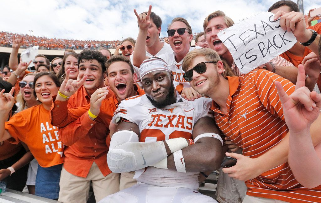 Texas Longhorns defensive lineman Charles Omenihu (90) poses with fans after the Longhorns' 48-45 win during the University of Texas Longhorns vs. the Oklahoma Sooners NCAA football game at the Cotton Bowl in Dallas on Saturday, October 6, 2018. (Louis DeLuca/The Dallas Morning News)
