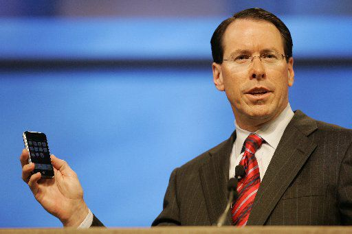 AT&T's Randall Stephenson, at that time the company's chief operating officer, shows off the new iPhone during a speech at a conference in 2007. (File Photo/The Associated Press)