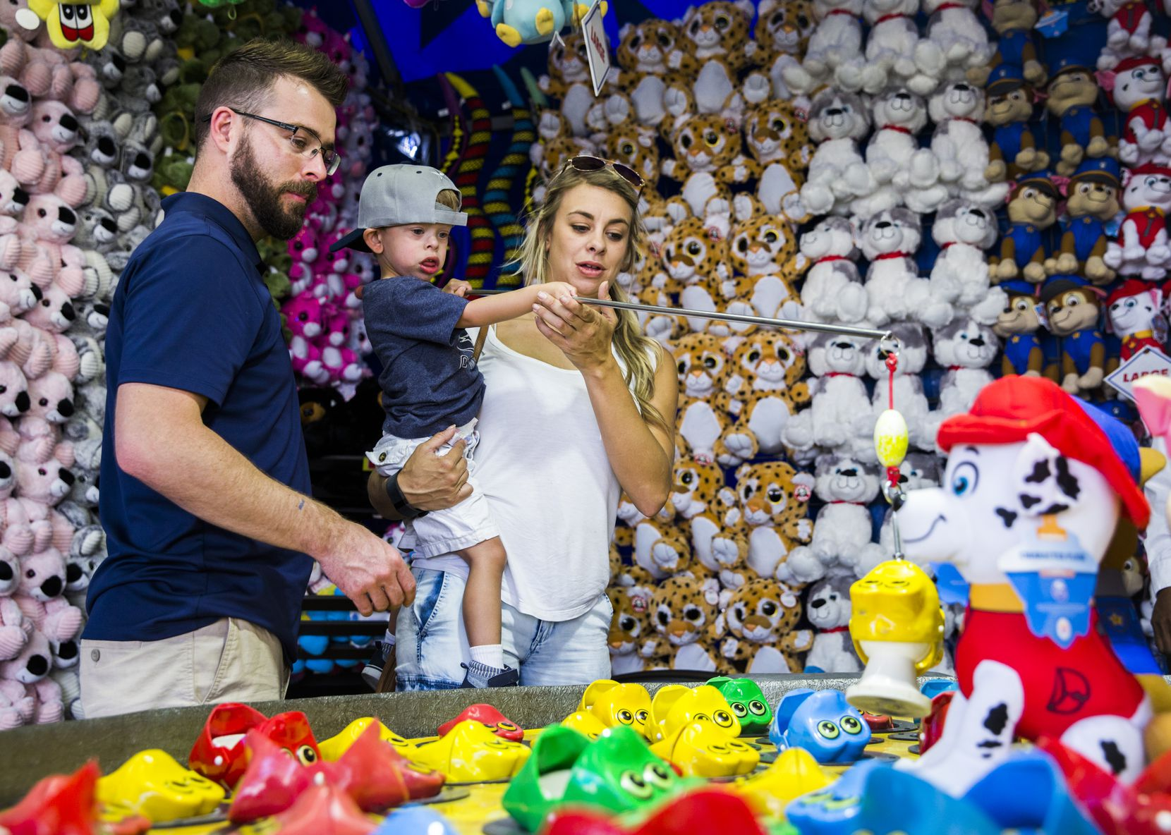 Natalie Janacek and Dustin Guess helped Luke Janacek, who was 3 years old at the time, as he played a carnival game at the State Fair of Texas in September 2017.