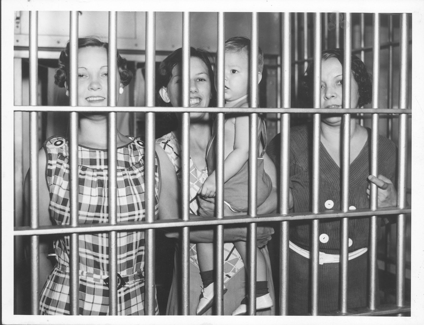 Charlotte Duncan, Jessie Burgett with son Roy, and May Sealey in the Dallas jail in 1935 for strike activities.