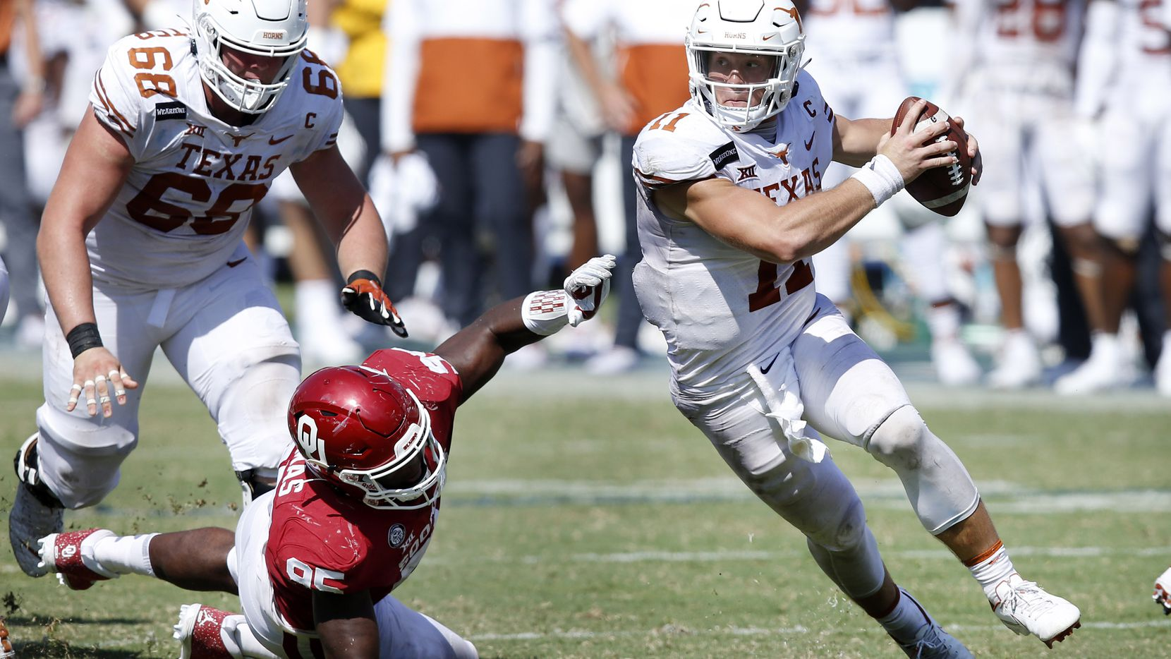 Texas Longhorns quarterback Sam Ehlinger (11) spins away from Oklahoma Sooners defensive lineman Isaiah Thomas (95) during the fourth quarter of the Red River Rivalry at the Cotton Bowl in Dallas, Saturday, October 10, 2020.