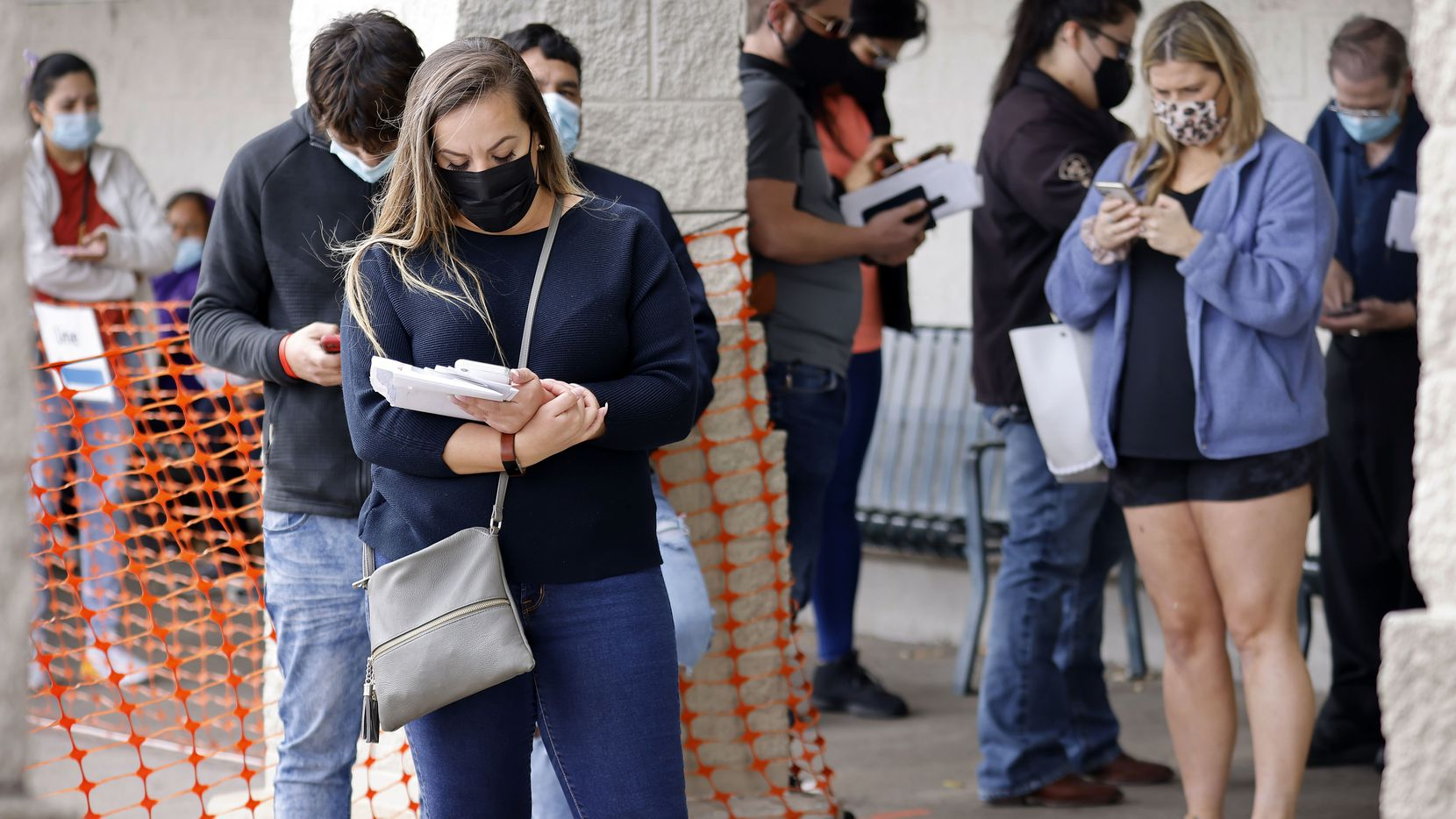 People wearing masks wait in line outside the Texas Department of Public Safety Drivers License Center in Garland, Texas, March 10, the first day of Governor Greg Abbott's lifting of the mask mandate and other restrictions.