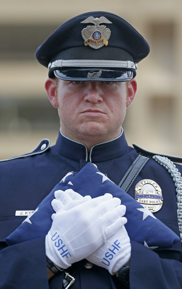 Joseph Kyser, a member of the DART Police Honor Guard (wearing official U.S. Honor Flag gloves), holds the Honor Flag during the Tribute 7/7 memorial event at Dallas City Hall Plaza in Dallas, Friday, July 7, 2017.