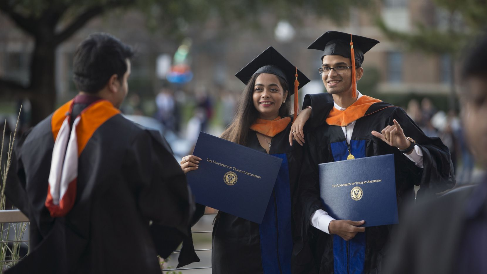Mrunmayee Kale of India, middle, and Avinash Gayam of India pose for a picture after graduation ceremonies at the University of Texas at Arlington in December 2018. At UTA, international students play a big role in research and discoveries, the provost said. (Daniel Carde/The Dallas Morning News)