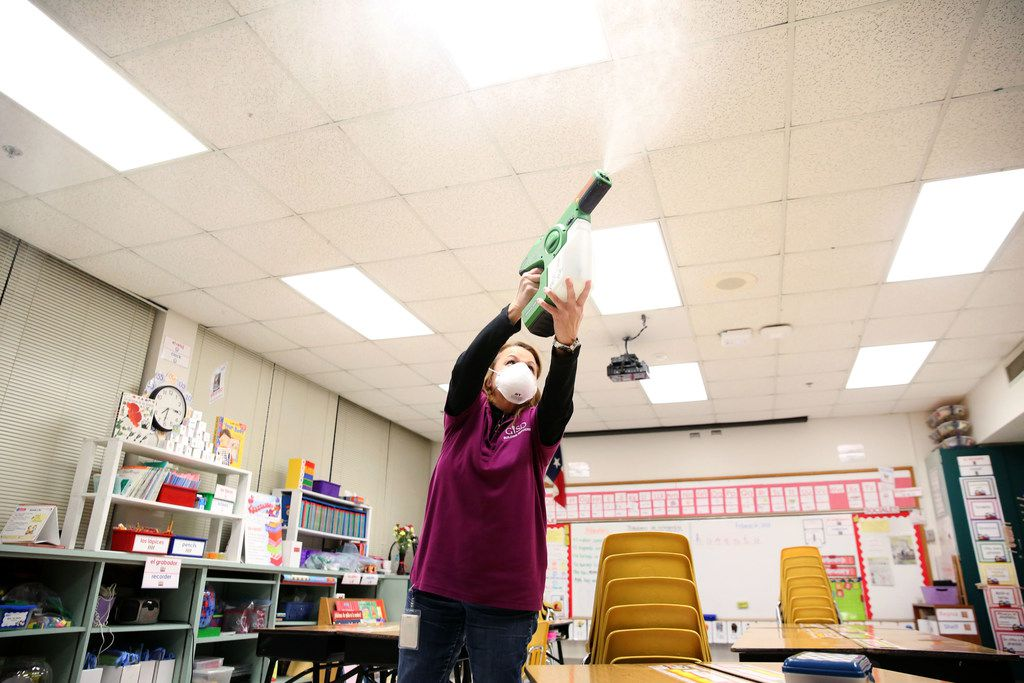 Celia Contreras, a custodian with Garland ISD, sprays a disinfectant in a classroom at Parkcrest Elementary School in Garland on Feb. 8.