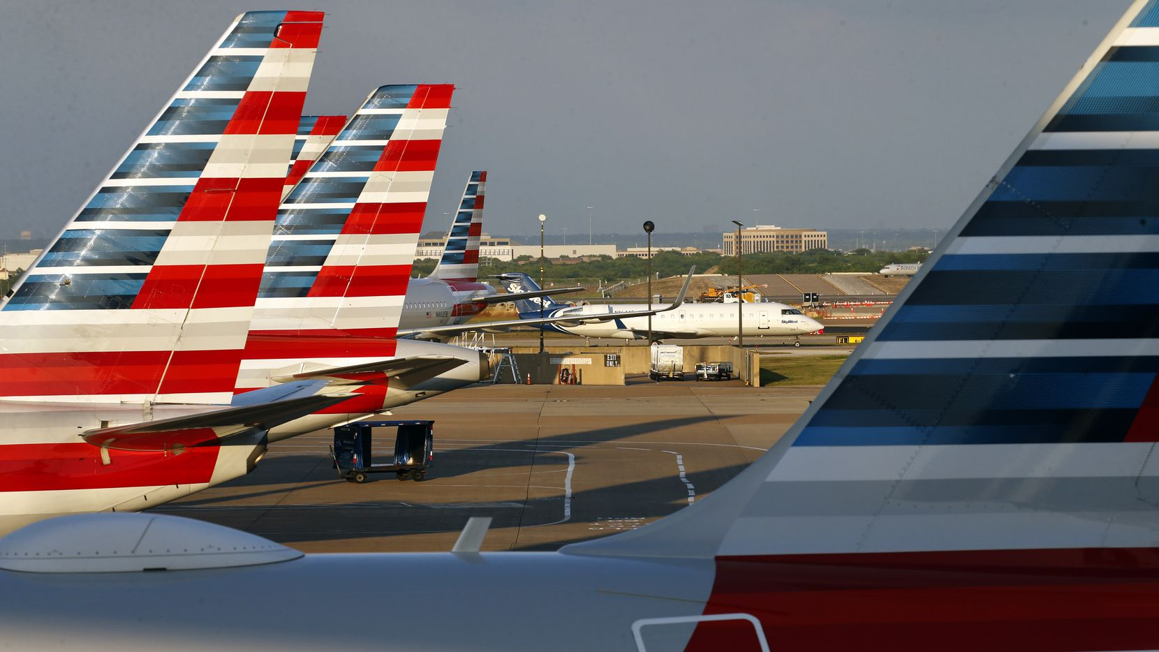 American Airlines jets are parked at Terminal C as a Skywest jet taxis to the gate at Dallas-Fort Worth International Airport.