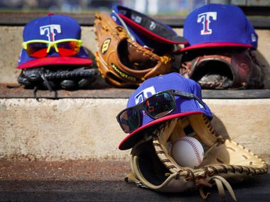Texas Rangers gloves, hats and glasses rest on a dugout step during the fourth inning of a spring training game against the Seattle Mariners at Peoria Sports Complex on Sunday, Feb. 23, 2020, in Peoria, Ariz.