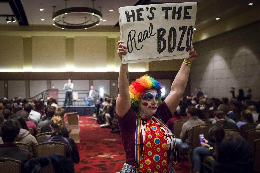 """Demonsrator Azzurra Crispino walks around the room in a clown suit holding a sign reading """"He's the Real Bozo"""" as Richard Spencer speaks at the Memorial Student Center at Texas A&M University on Tuesday, Dec. 6, 2016, in College Station, Texas. Spencer, a Dallas native and a self-professed founder of the """"alt right"""" movement, will speak at the campus at the invitation of a white nationalist and former student.  The university hosted the Aggies United event at Kyle Field, the university's football stadium, to overlap with Spencer's speech. (Smiley N. Pool/The Dallas Morning News)"""