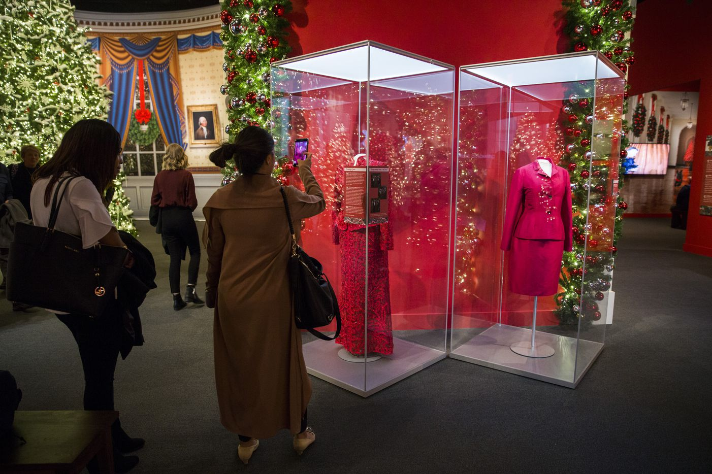 Visitors take photos of a red Oscar de la Renta evening gown worn by Laura Bush is displayed at a Christmas exhibit at The George W. Bush Presidential Center and Library on Thursday, November 15, 2018 on the SMU campus in Dallas. This year's theme is Deck the Halls and Welcome All: Christmas at the White House 2006. When the Bushes arrived at their White House Christmas party, Laura noticed three of her friends wearing the same dress. She changed clothes before the party. (Ashley Landis/The Dallas Morning News)