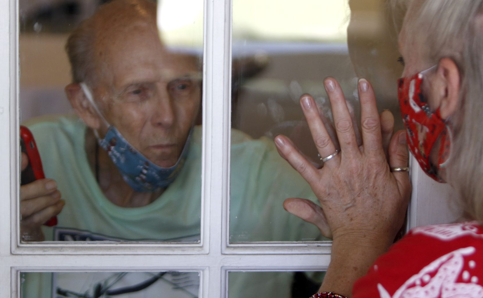 """Richard """"Captain"""" Playter and family friend Diane Cannon touch hands on either side of a glass window at Caruth Haven Court in Dallas."""