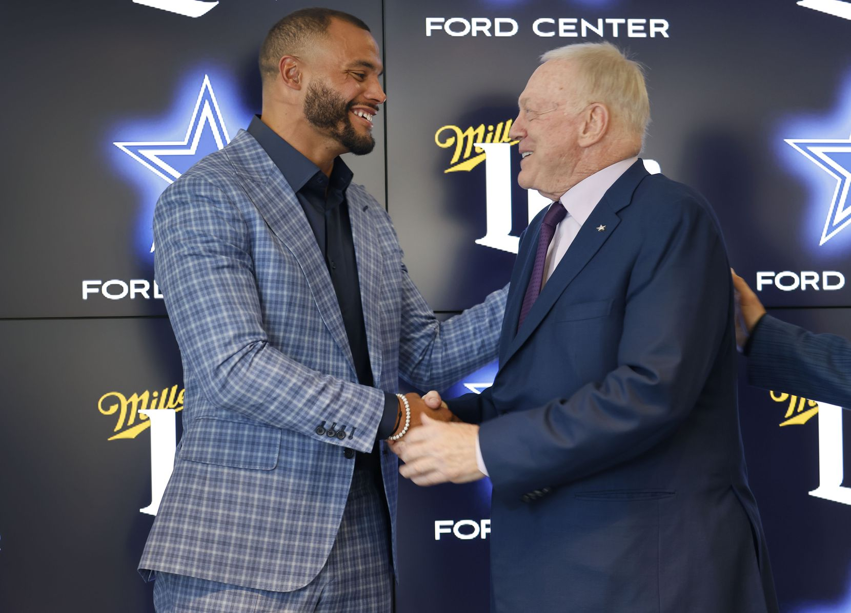 Dallas Cowboys quarterback Dak Prescott (left) and Dallas Cowboys owner Jerry Jones shake hands following a press conference at The Star in Frisco, Texas, Wednesday, March 10, 2021.