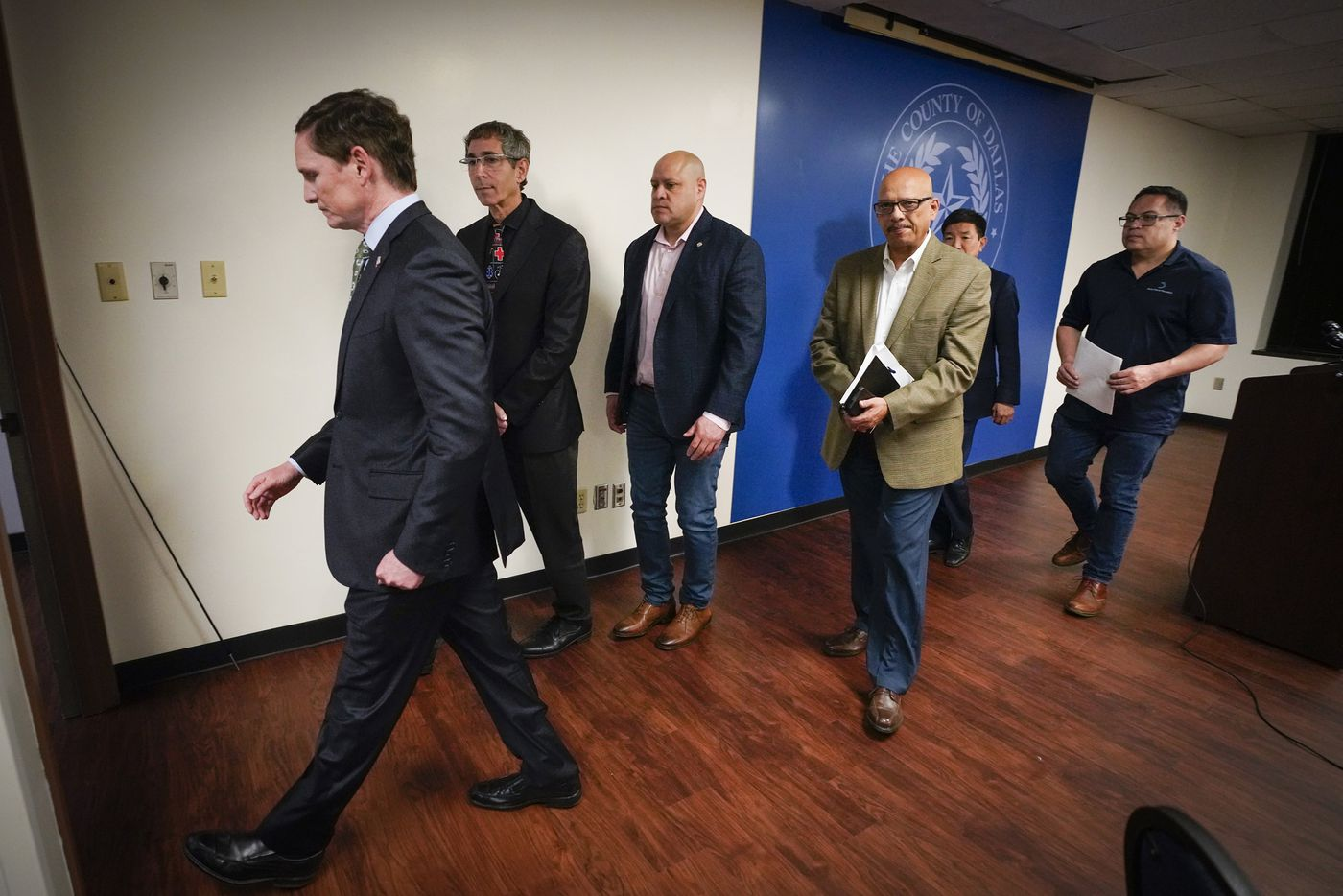 Dallas County Judge Clay Jenkins (left) departs a press conference with other city and county officials after announcing that a local state of disaster for public health emergency has been declared in the county, due to more cases of the new coronavirus, late Thursday, March 12. 2020, in Dallas. With him, from left, are Dr. Marshal Isaacs, Dallas Mayor Pro Tem Adam Medrano​, Rocky Vaz, City of Dallas Director of Emergency Management, Dr. Philip Huang, Director of Dallas County Health and Human Services, and Dallas city council member Omar Narvaez.