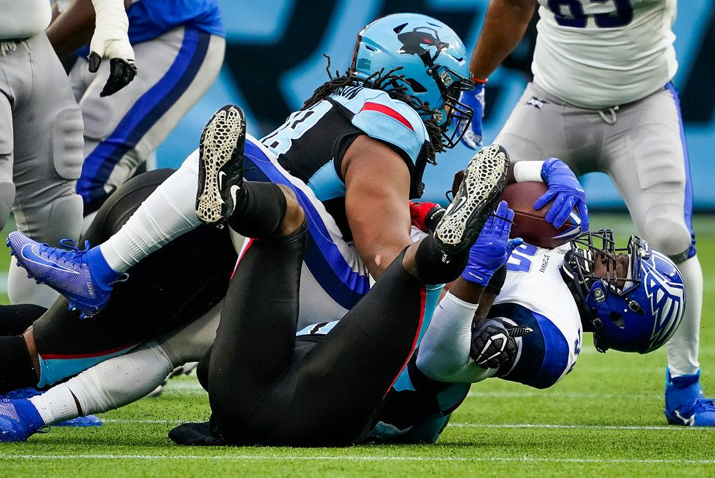 St. Louis Battlehawks running back Christine Michael (33) is brought down by Dallas Renegades linebacker Tegray Scales (46) and defensive end Gelen Robinson (98) during the first half of an XFL football game at Globe Life Park on Sunday, Feb. 9, 2020, in Arlington.