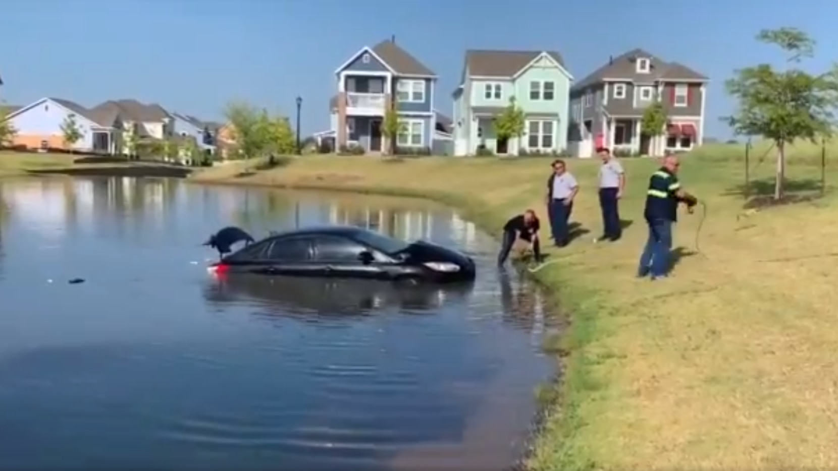 A black sedan is towed from a lake in North Richland Hills by officials Wednesday morning.