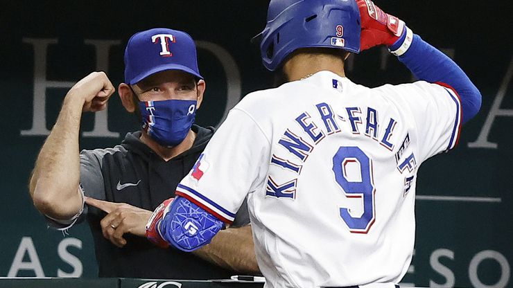 Texas Rangers manager Chris Woodward flexes his muscle as he congratulates Isiah Kiner-Falefa (9) on his solo home run against the Boston Red Sox in the seventh inning at Globe Life Field in Arlington, Texas, Thursday, April 29, 2021. (Tom Fox/The Dallas Morning News)