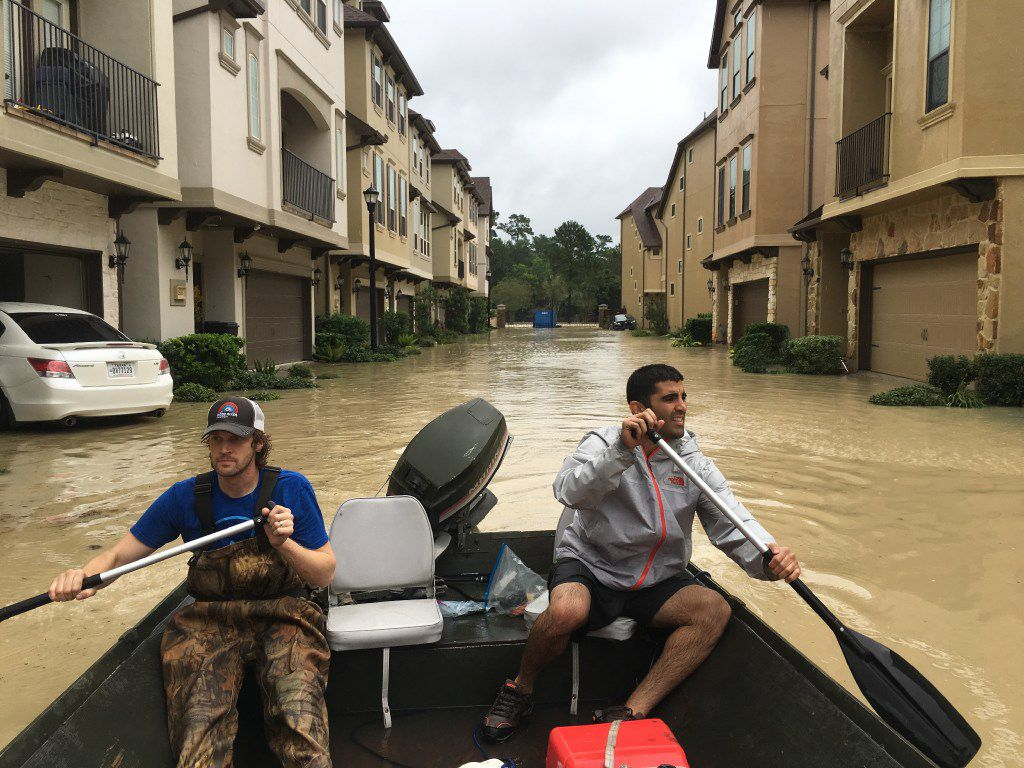 Dallas residents Josh Womack and Sammy Abdullah paddle through a row of townhomes on a search-and-rescue trip in the Kingwood neighborhood of Houston on Aug. 29.