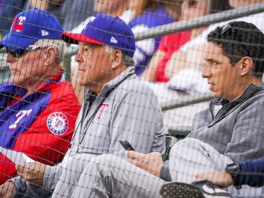 FILE - Rangers GM Jon Daniels (right) watches a spring training game with co-chairman and managing partner Ray C. Davis (left) and chairman, ownership committee and chief operating office Neil Leibman (center) at Surprise Stadium on Thursday, Feb. 27, 2020, in Surprise, Ariz.