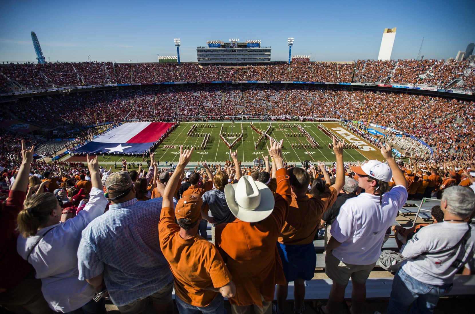 Texas Longhorns fans hookem as the Texas Longhorns band takes the field before the 2016 AT&T Red River Showdown between the Texas Longhorns and the Oklahoma Sooners at the Cotton Bowl in Fair Park.