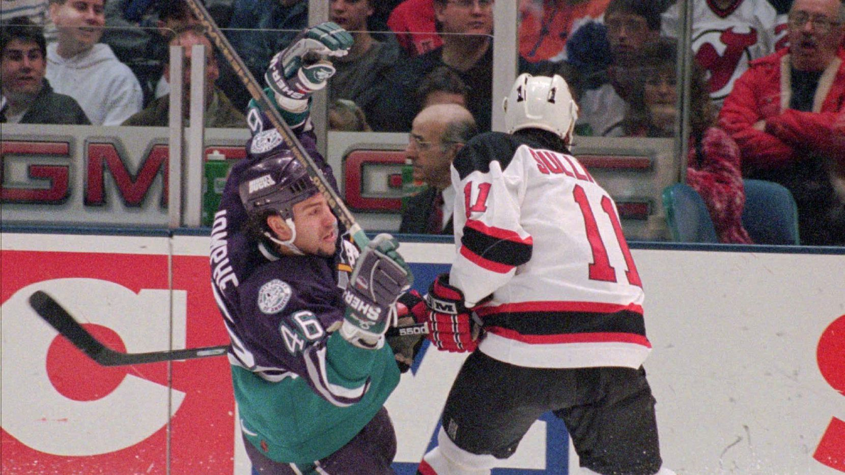 Anaheim Mighty Ducks' J.F. Jomphe (46) is checked to the ice by New Jersey Devils' Steve Sullivan (11) during a 1996 game.