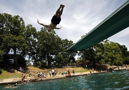 Todd Mouser of Los Angeles California dives at Barton Springs Pool on Friday afternoon during free swim day.