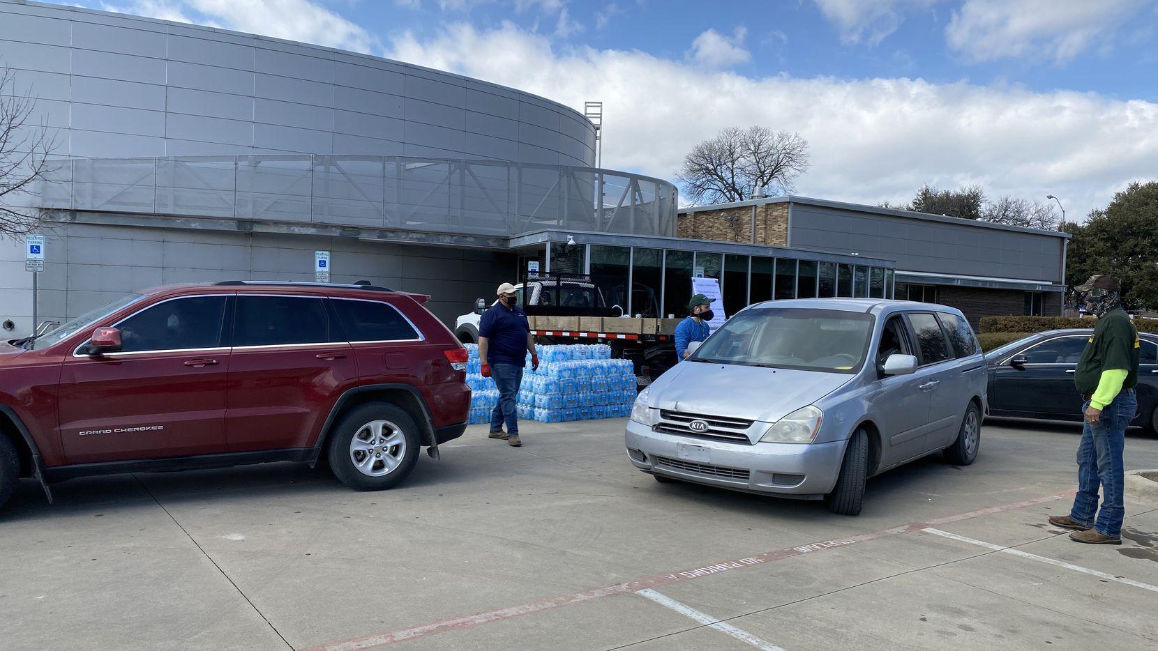 Los residentes hicieron desde sus vehículos para una repartición de agua el domingo en West Dallas.