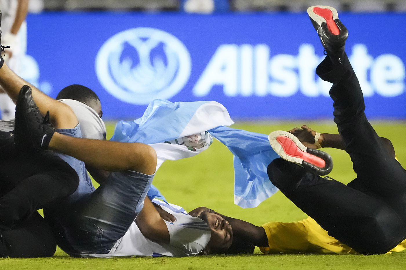 Security guards tackle a fan carrying a Guatemala flag as he runs during the second half of a CONCACAF Gold Cup Group A soccer match against Mexico at the Cotton Bowl on Wednesday, July 14, 2021, in Dallas.