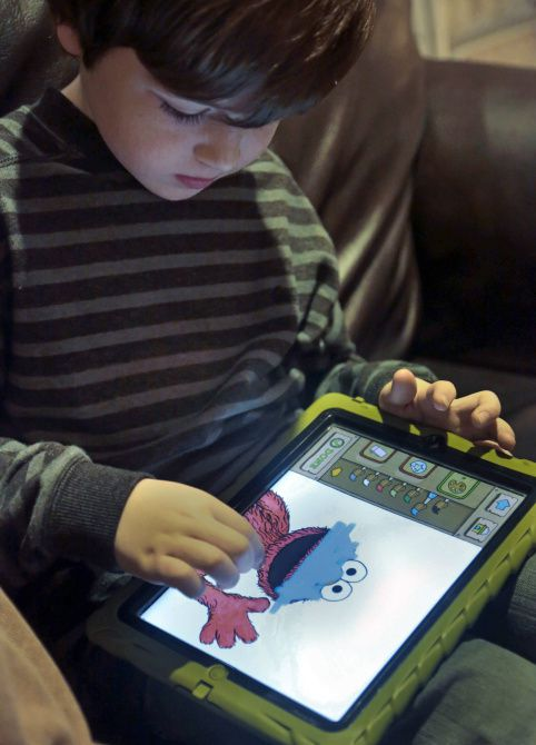 Marc Cohen, 5, uses a Sesame Street app at home in New York. His dad says apps help Marc learn, but experts are cautious.