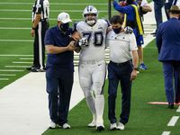 Dallas Cowboys offensive guard Zack Martin is helped off the field after being injured during the first quarter of an NFL football game against the Washington Football Team at AT&T Stadium on Thursday, Nov. 26, 2020, in Arlington.
