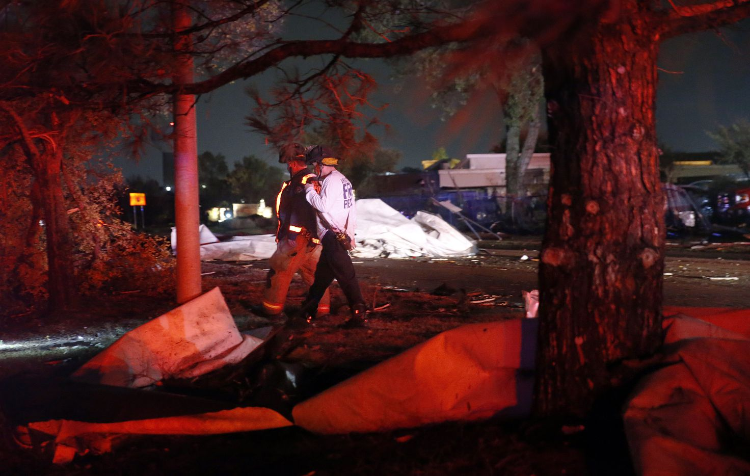 A pair of firefighters inspect the damage after the roofs of The Mirage Apartments complex were torn off and landed on Pioneer Parkway in Arlington following a tornado-warned storm, Tuesday night, November 24, 2020.