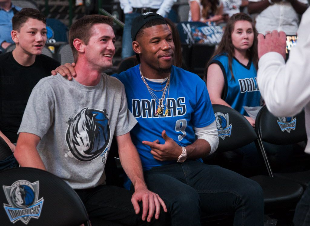 Dallas Cowboys wide receiver Terrance Williams, center, poses with a fan during halftime of an NBA game between the Dallas Mavericks and the Denver Nuggets on Tuesday, April 11, 2017 at the American Airlines Center in Dallas. (Ashley Landis/The Dallas Morning News)
