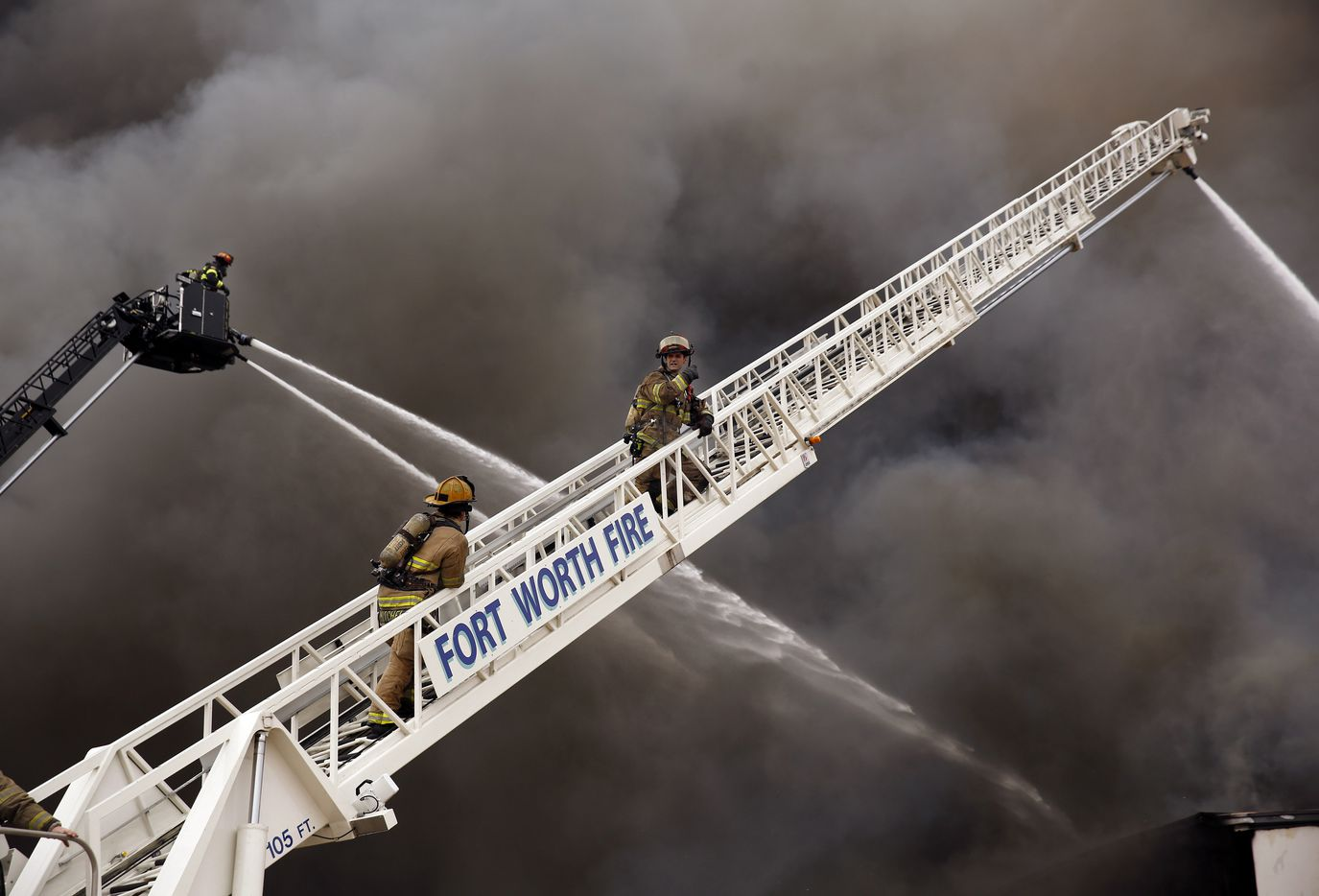 Fort Worth Fire Department Captain Jacob Henderson, right, and Connor Mitchell climb an aerial ladder as they and multiple fire departments respond to a large, 5-alarm fire at the Advanced Foam Recycling facility in Richland Hills, Texas, Thursday, February 25, 2021. Advanced Foam Recycling recycles materials to be processed and used for carpet underlay, pillows, and furniture, according to the company website. Over 125  firefighters from Richland Hills, Haltom City, North Richland Hills and Fort Worth firefighters assisted on the commercial structure fire in the 2500 block of Handley Ederville Road in E. Fort Worth. (Tom Fox/The Dallas Morning News)