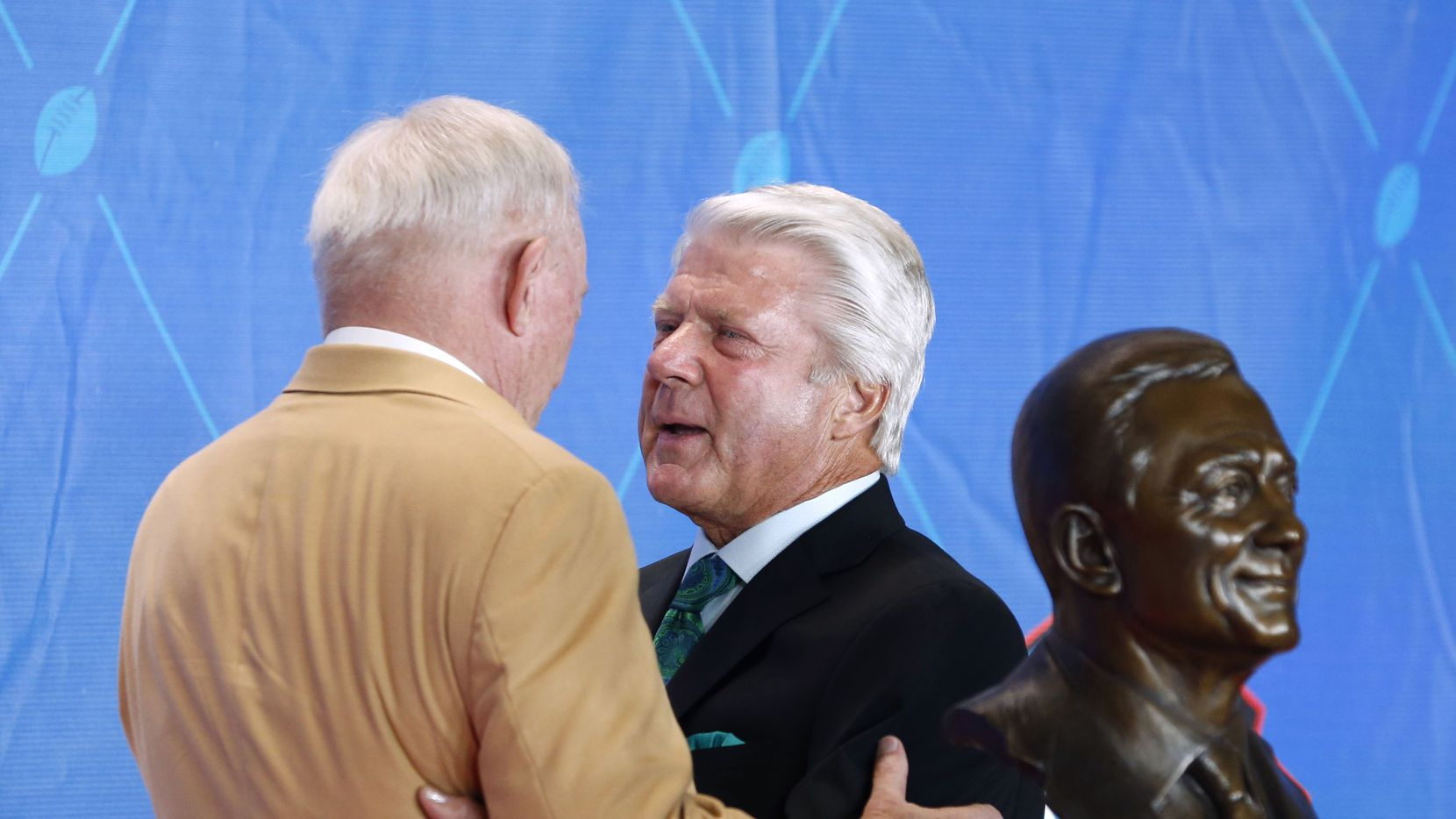 Former Dallas Cowboys head coach Jimmy Johnson talks with 2017 Pro Football Hall of Fame inductee and Dallas Cowboys owner and general manager Jerry Jones at the 2017 Pro Football Hall of Fame Enshrinement Ceremony at Tom Benson Stadium in Canton, Ohio on Saturday, August 6, 2017.