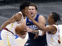Dallas Mavericks guard Luka Doncic (77) splits a pair of Cleveland Cavaliers defenders for a second quarter shot at the American Airlines Center in Dallas, Friday, May 7, 2021.