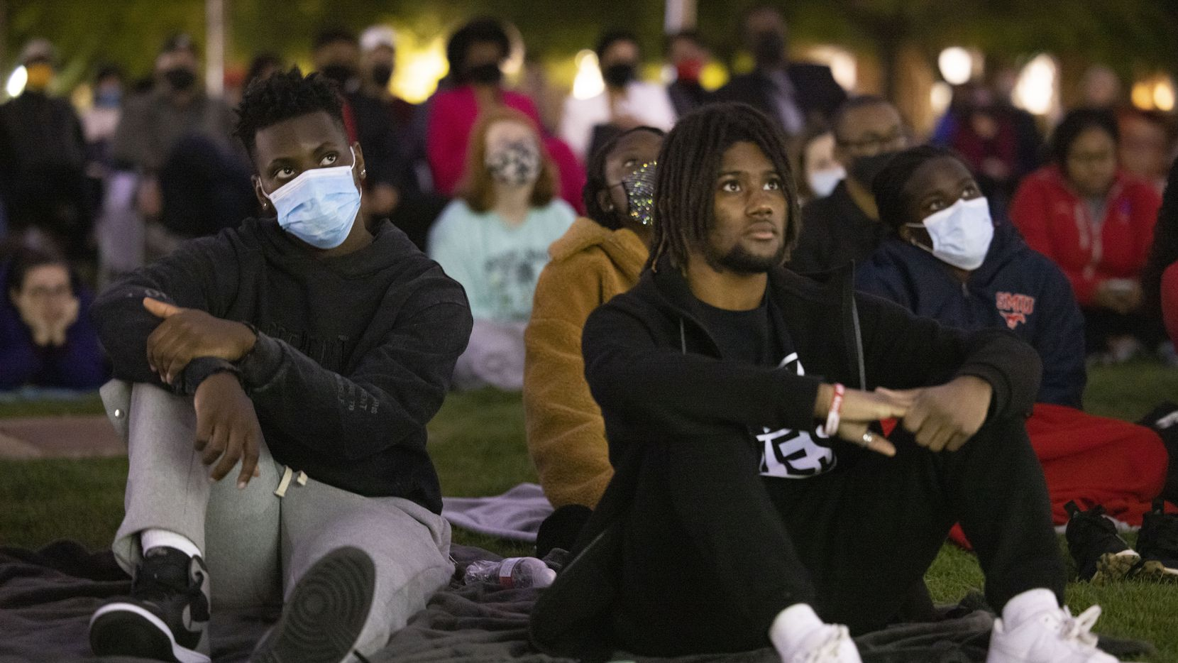 (From left) Students Ogheneferga Evuarherhe and Matthieu Legagneur watch the #BlackAtSMU film, which documents five Black students' encounters with racism at SMU, at the Dallas Hall Lawn on SMU's campus on Wednesday.