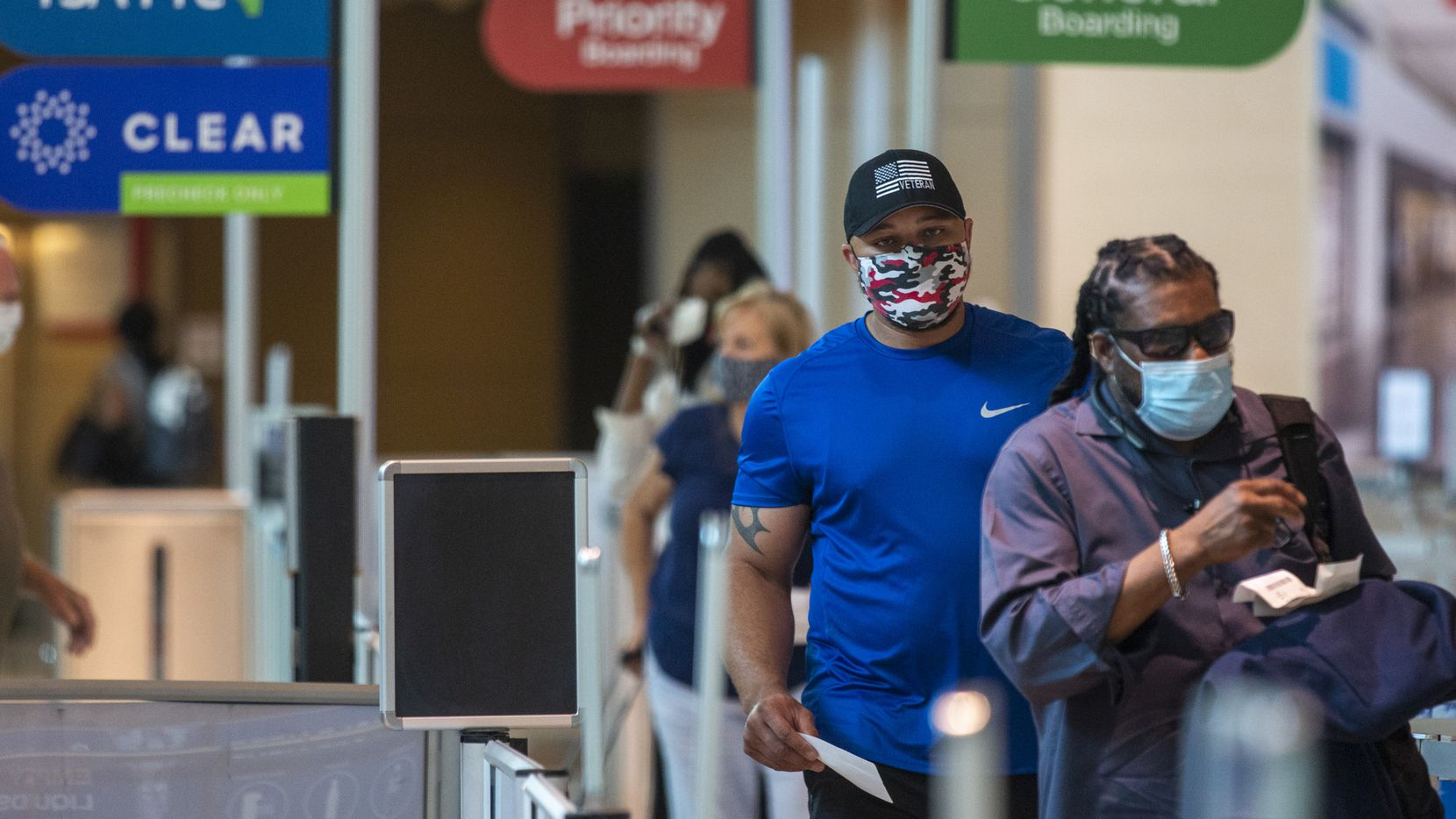 Masked passengers walk to the security checkpoint at Dallas Love Field airport in Dallas on Sunday, July 26, 2020. (Lynda M. Gonzalez/The Dallas Morning News)