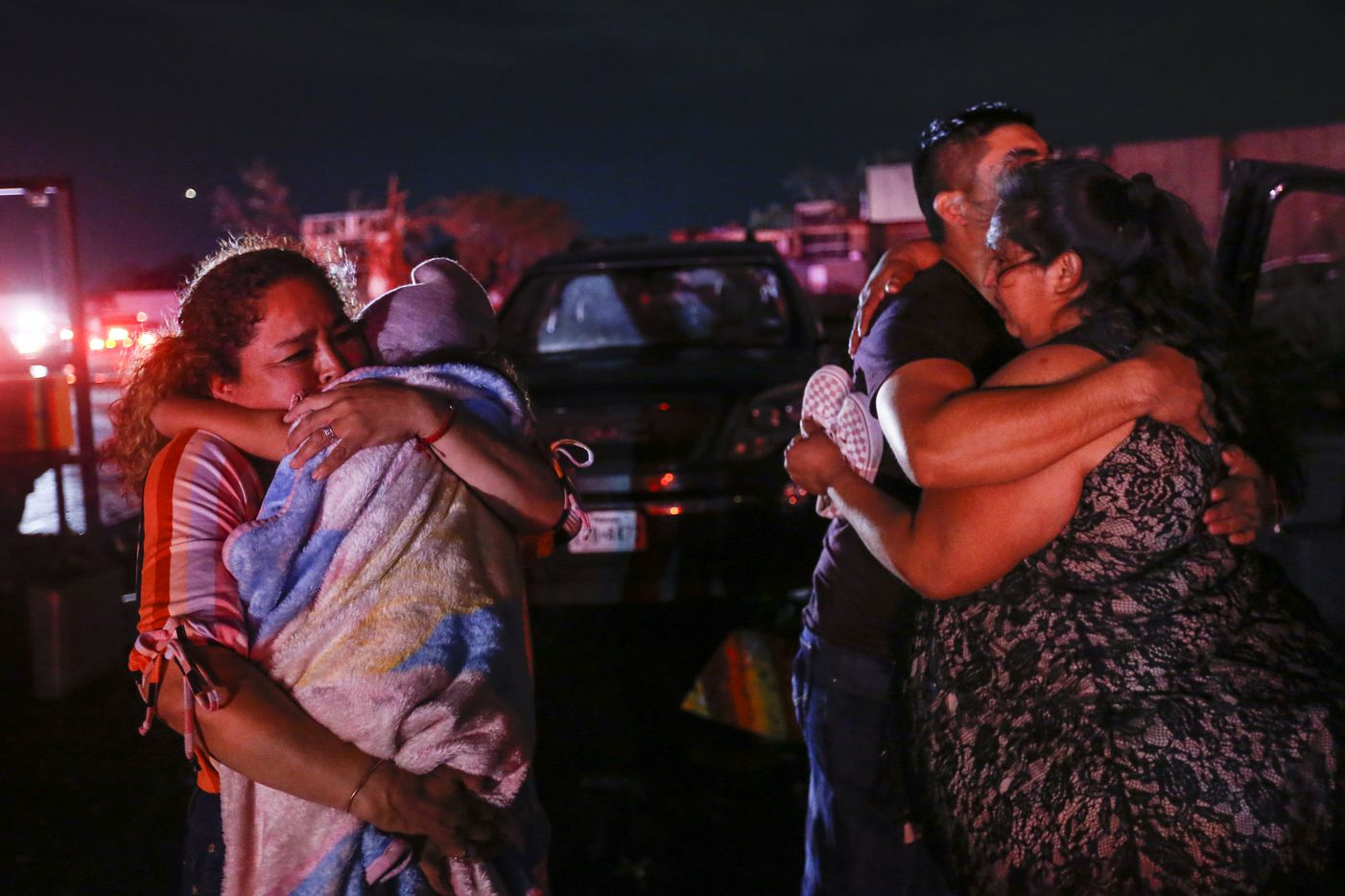 Family members embrace after reuniting after a storm near the intersection of Walnut Hill Lane and Marsh Lane in Dallas where a storm hit Sunday, Oct. 20, 2019.