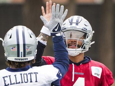 Dallas Cowboys quarterback Dak Prescott (4) high fives running back Ezekiel Elliott (21) during a practice at training camp on Sunday, July 25, 2021, in Oxnard, Calif.