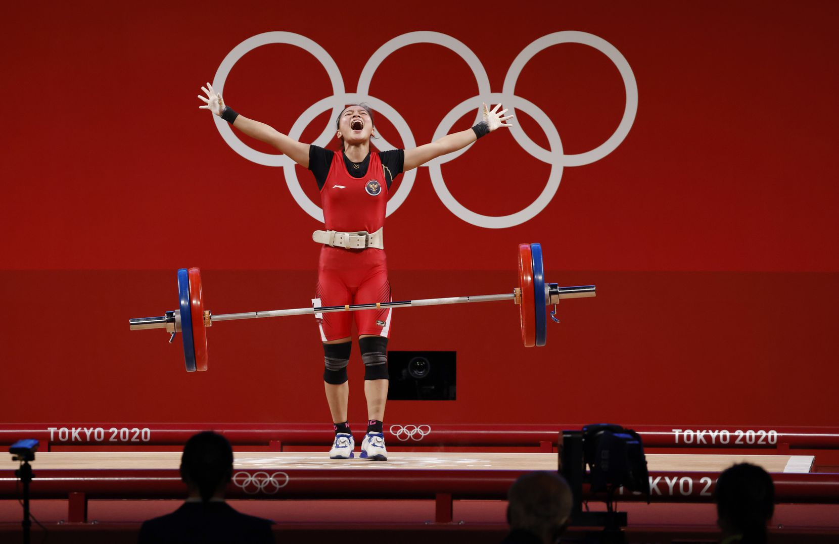 Indonesia's Windy Cantika Aisah celebrates after a successful clean and jerk of 110 kg in her third attempt in the clean and jerk round during the women's 49 kg weightlifting final during the postponed 2020 Tokyo Olympics at Tokyo International Forum on Saturday, July 24, 2021, in Tokyo, Japan. Aisah won a bronze medal in this event. (Vernon Bryant/The Dallas Morning News)