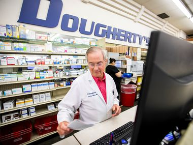 Pharmacist Jim Hawkins works behind the counter  at the flagship Dougherty's Pharmacy in Preston Royal Village.