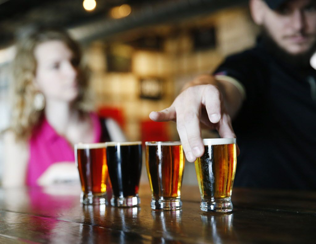 Bailey Yancy (left) looks on as Justin Villarreal (right), both of Denton, Texas, picks up a beer sample at the bar while brewery tours are offered at the Four Corners Brewing Co. in Dallas Saturday September 27, 2014.
