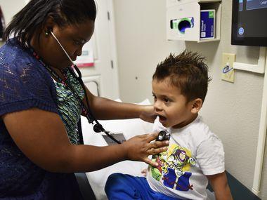 La enfermera Chandra Smith (izq.) escucha la respiración de Matías Bonilla, de3 años, durante una visita médica a la Clínica Agape en Dallas.